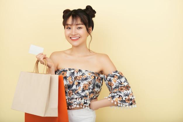 Plano medio de niña asiática de pie con bolsas de compra y tarjeta de crédito sonriendo