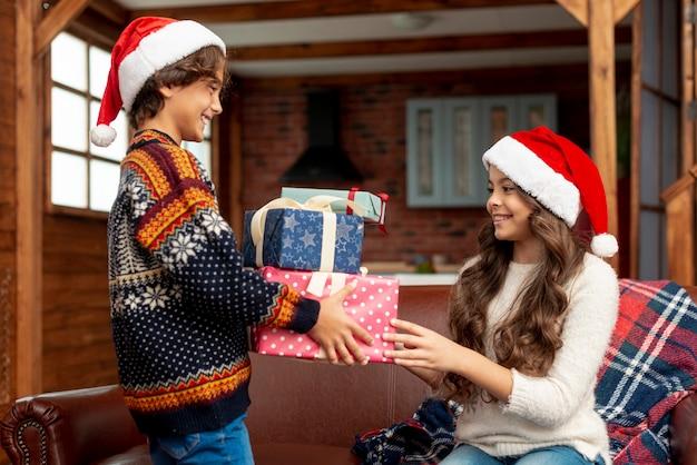 Plano medio, niña y niño felices compartiendo regalos
