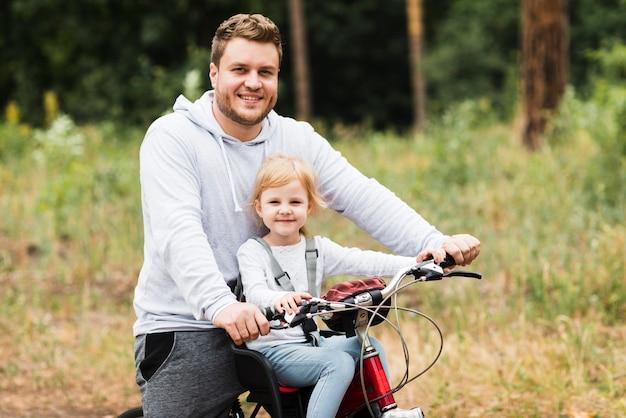 Plano medio padre e hija en bicicleta