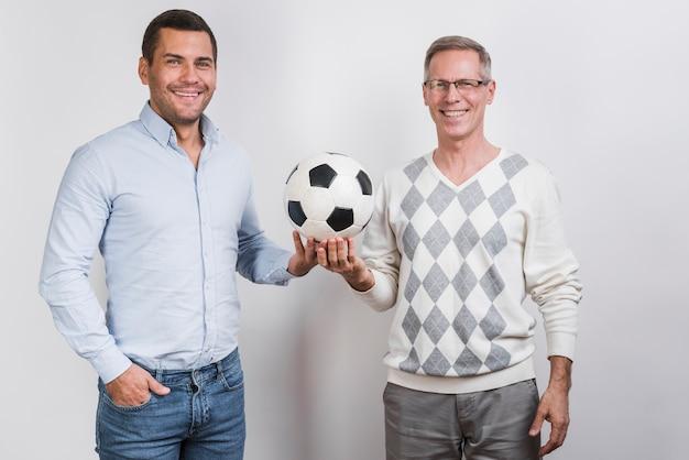 Plano medio de padre e hijo sosteniendo una pelota de fútbol