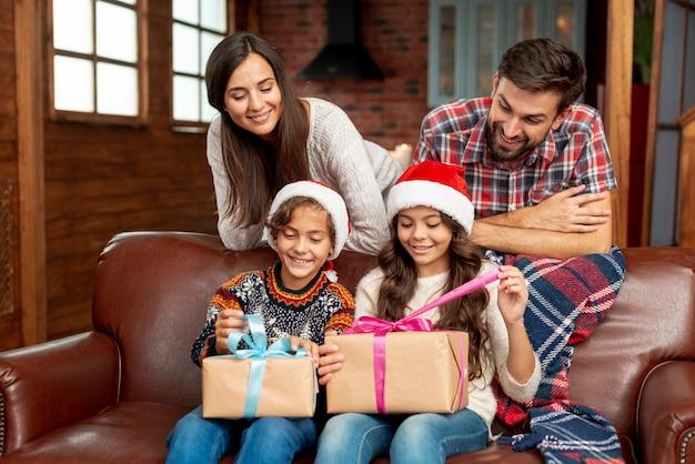 Plano medio padres felices mirando niños