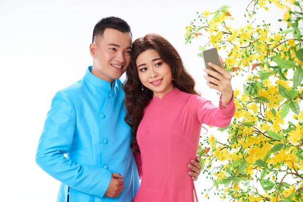 Plano medio de pareja asiática tomando selfie festival de primavera