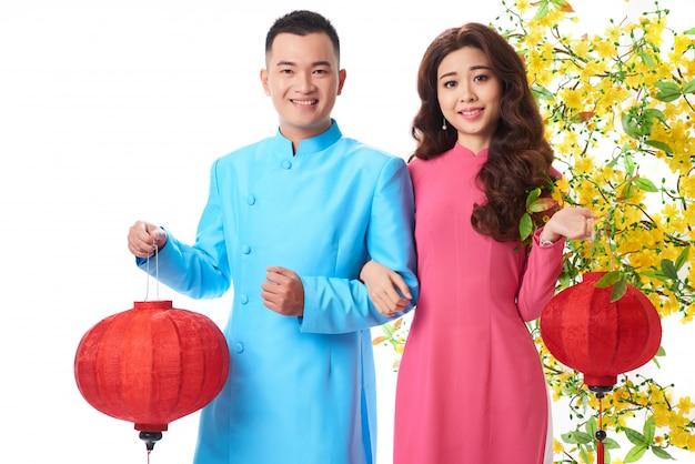 Plano medio de una pareja asiática en trajes tradicionales con linternas rojas