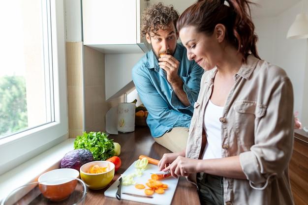 Plano medio de pareja durante la cena cocinando