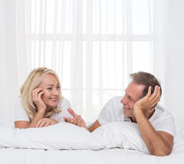 Plano medio pareja charlando en el dormitorio