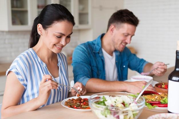 Plano medio pareja comiendo juntos