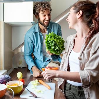 Plano medio de la pareja divirtiéndose durante la cocción