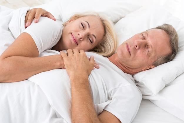 Plano medio pareja durmiendo juntos