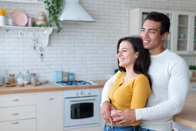 Plano medio de una pareja encantadora en la cocina.