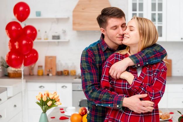Plano medio pareja feliz abrazando en la cocina