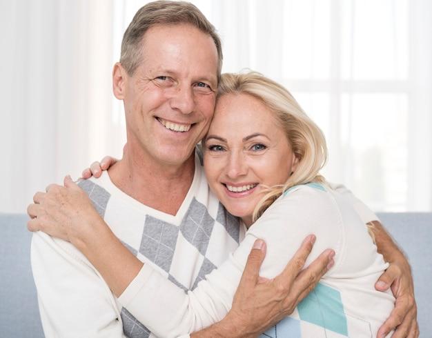 Plano medio pareja feliz abrazando en el interior