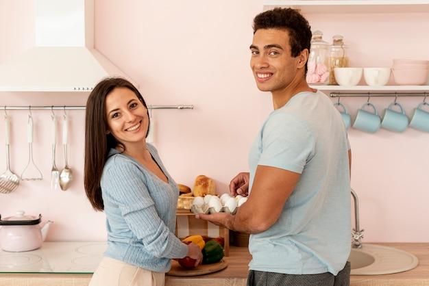 Plano medio pareja feliz con caja de huevos