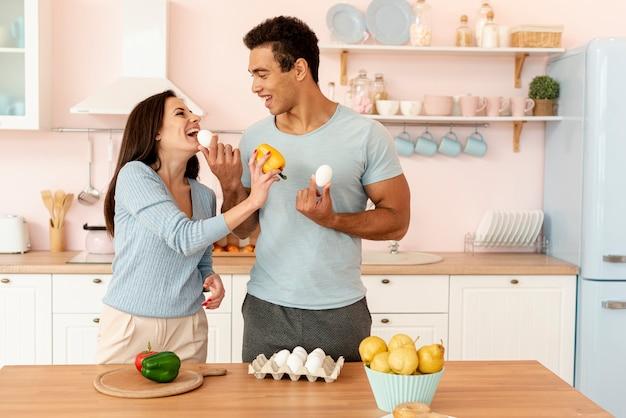 Plano medio pareja feliz cocinando juntos
