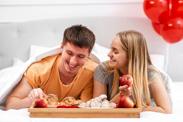 Plano medio pareja feliz comiendo en la cama