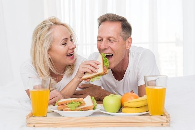 Plano medio pareja feliz comiendo juntos