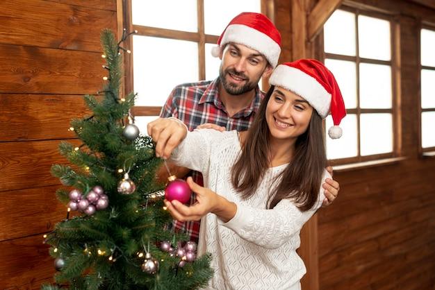 Plano medio pareja feliz decorando el árbol de navidad