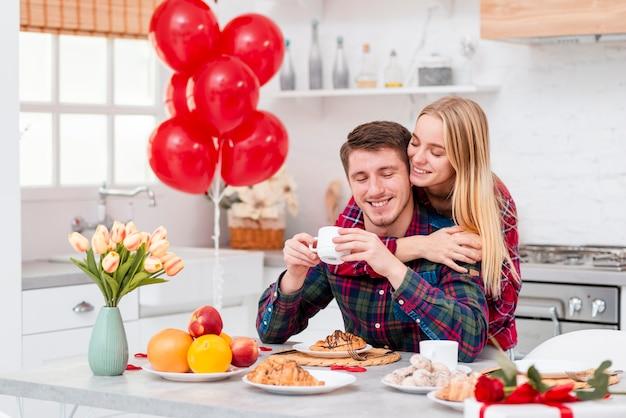 Plano medio pareja feliz con desayuno en la cocina