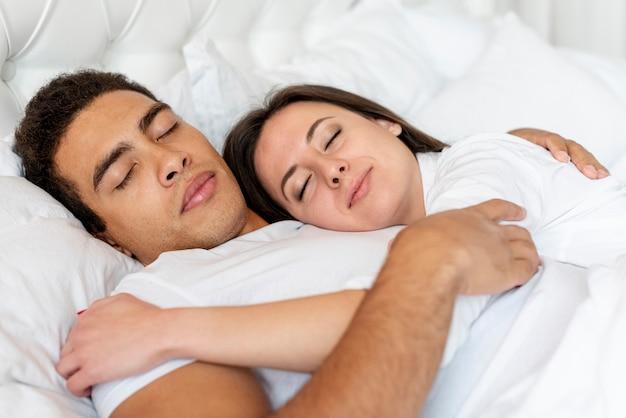 Plano medio pareja feliz durmiendo juntos
