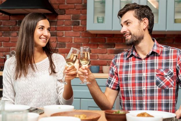 Plano medio pareja feliz haciendo un brindis