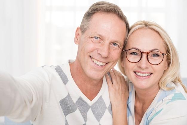 Plano medio pareja feliz tomando una selfie