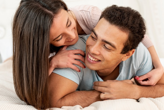 Plano medio pareja sentada en la cama