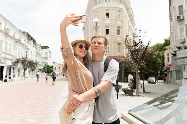 Plano medio pareja tomando selfie