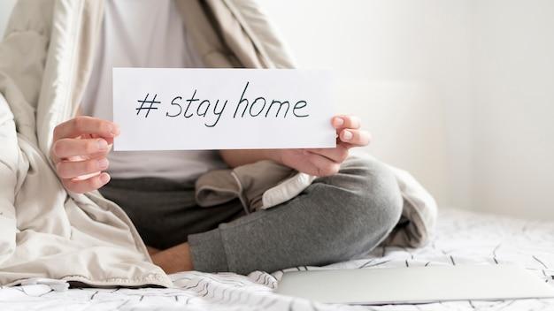 Plano medio de una persona enferma con un cartel de quedarse en casa