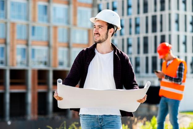 Plano medio retrato de arquitecto sosteniendo planes