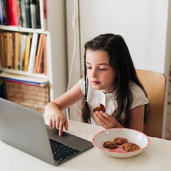 Plano medio sentado a la mesa con galletas