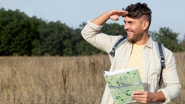 Plano medio sonriente hombre sujetando mapa