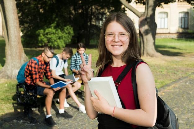 Plano medio de sonriente niña de secundaria sosteniendo un libro en las manos