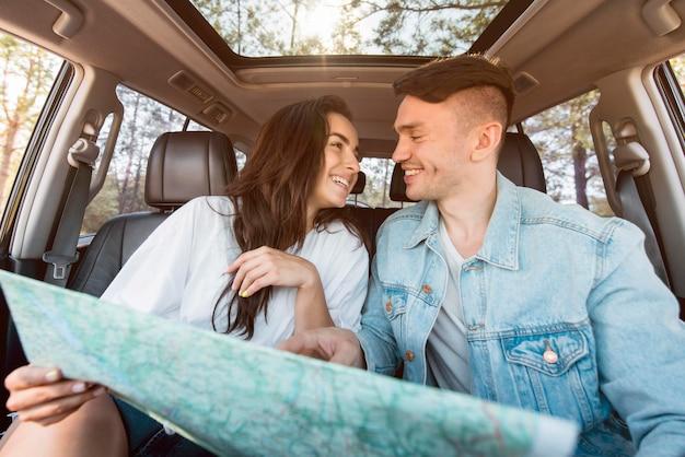 Plano medio sonriente pareja sosteniendo mapa