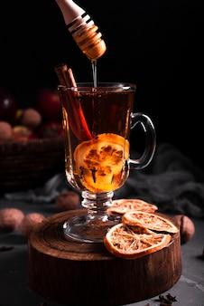 Plano medio de té caliente con miel.
