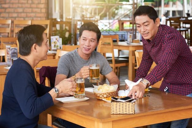 Plano medio de tres amigos tomando cerveza en el bar