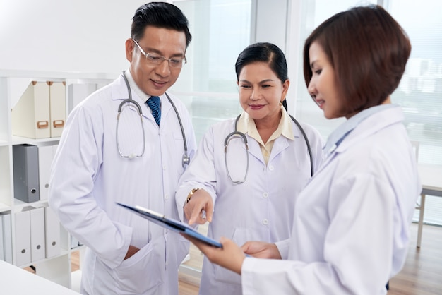 Plano medio de tres médicos que analizan la lista de síntomas