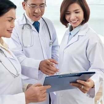 Plano medio de tres médicos que consultan sobre un caso médico