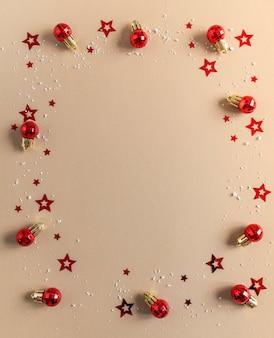Plano de navidad con bolas rojas de navidad, confeti y nieve artificial sobre un fondo beige. vista superior. copia espacio
