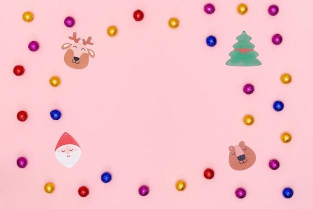 Plano de navidad con caramelos de chocolate, estrellas decorativas, copo de nieve, santa y árbol de navidad en papel rosa