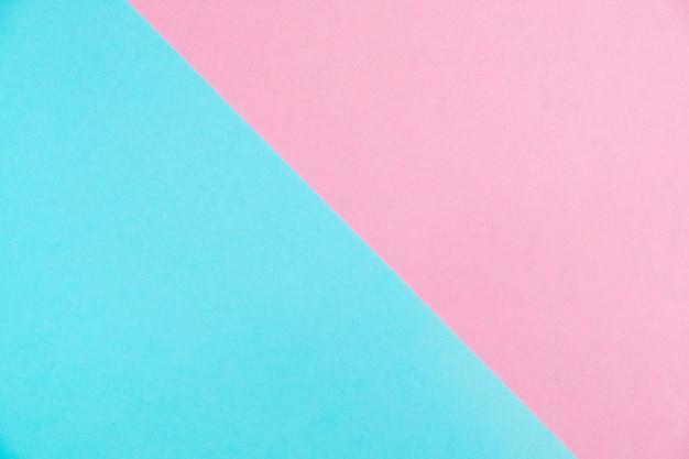 El plano de papel coloreado en colores pastel pone la visión superior, la textura del fondo, el rosa y el azul.