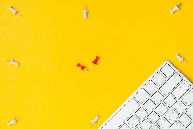 Plano plano del espacio de trabajo de escritorio, alfiler de empuje blanco, alfiler rojo y teclado con espacio en blanco sobre fondo amarillo