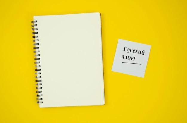 Plano pone cuaderno vacío sobre fondo amarillo