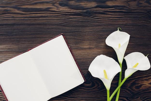 Plano pone flores blancas y diario sobre madera, vista desde arriba. bosquejo