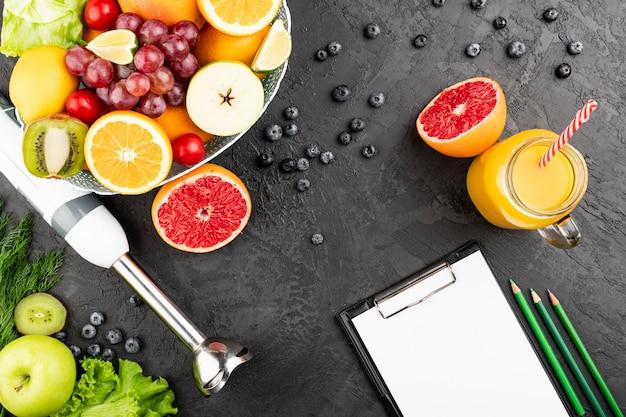 Plano pone jugo de naranja y tazón de fruta