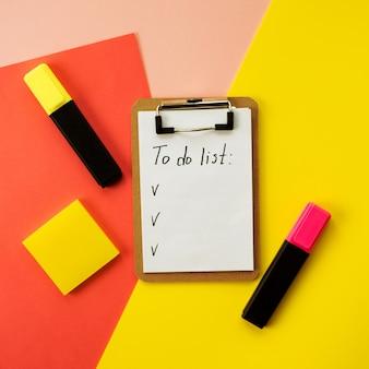 Plano del portapapeles con la lista de tareas en el papel blanco. fondo colorido de colores rosa, amarillo y coral. dos marcadores y goma de borrar al lado.