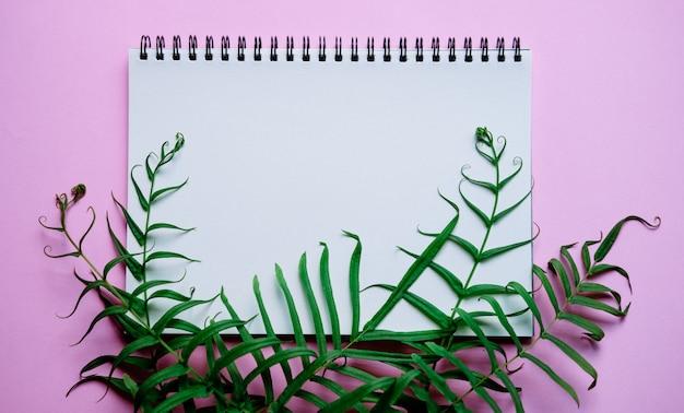 Plano puesto de escritorio de espacio de trabajo mínimo con cuaderno y planta verde