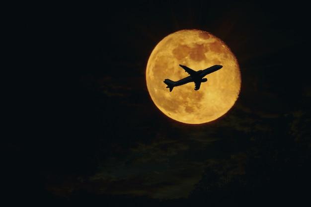 Plano, silueta de avión contra luna llena.