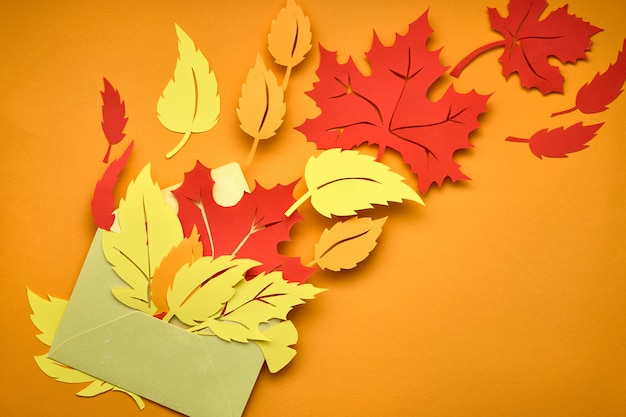 Plano sobre oscuro con hojas de papel rojo y naranja en el sobre
