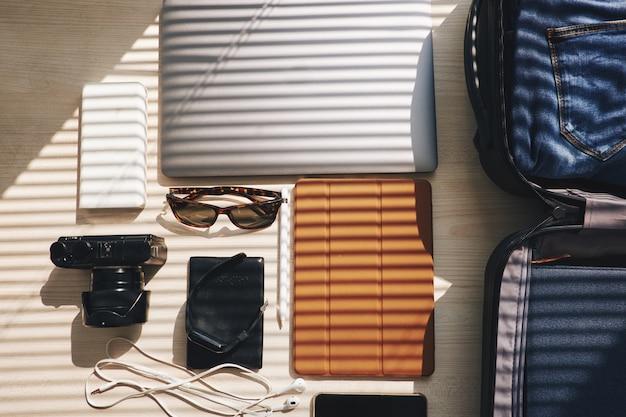 Plano superior de dispositivos electrónicos y maleta sobre la mesa, listo para un viaje de negocios
