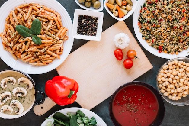 Plano de tabla de cortar con ajo y tomates cherry