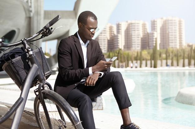 Plano urbano del empresario afroamericano confiado con gafas de sol redondas y elegante traje negro sentado al aire libre con su bicicleta, usando un teléfono móvil, revisando el correo electrónico y tratando asuntos comerciales